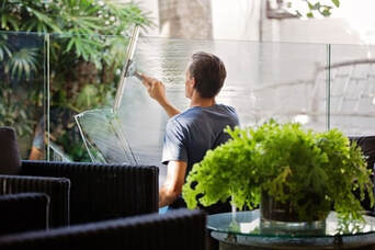 man-in-gray-shirt-cleaning-clear-glass-wall-near-sofa-384-256.jpg